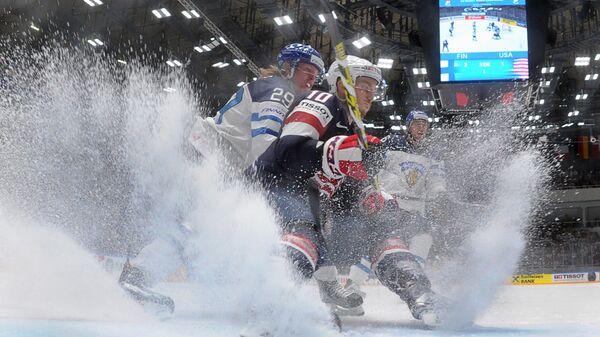 Игрок сборной Финляндии Патрик Лайне и игрок сборной США Джордан Шрёдер в матче группового этапа чемпионата мира по хоккею между сборными командами Финляндии и США