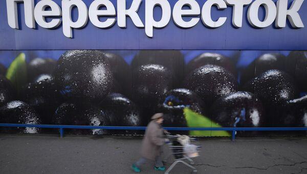 Женщина везет тележку с продуктами у супермаркета торговой сети Перекресток на Славянском бульваре в Москве
