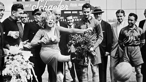 Американская актриса Мэрилин Монро отбивает мяч во время футбольного матча в Бруклине. 1957 год. Архивное фото.