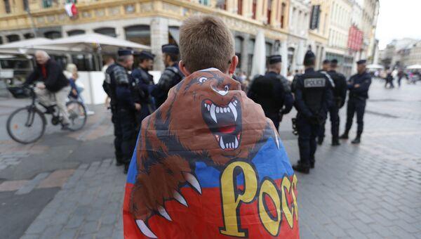 Российский болельщик рядом с сотрудниками полиции на улице в Лилле, Франция. 14 июня 2016