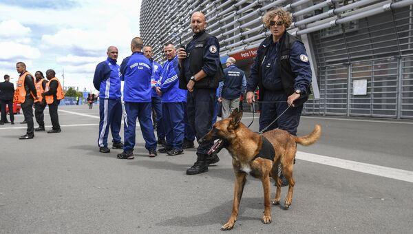Сотрудники полиции со служебной собакой у стадиона