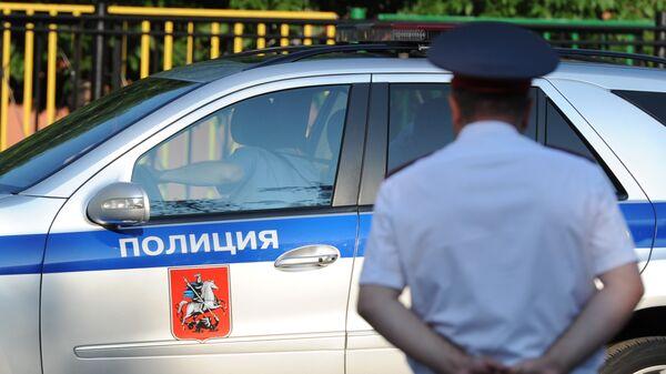 Полицейский автомобиль и сотрудник полиции в Москве