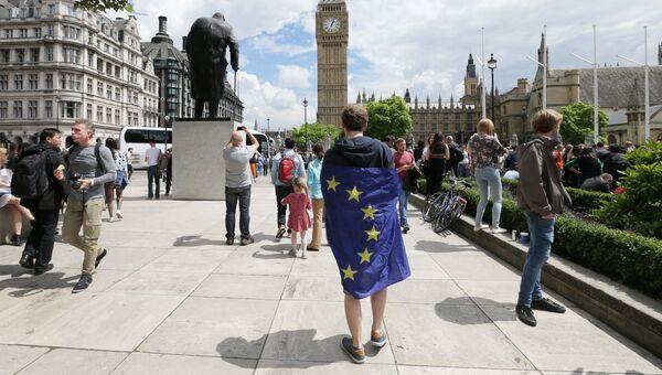 Мужчина с флагом ЕС на Парламентской площади Лондона, Великобритания. 25 июня 2016. Архивное фото