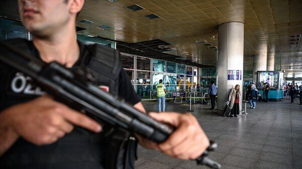 Сотрудник правоохранительных органов Турции месте теракта в аэропорту Стамбула. 29 июня 2016. Архивное фото