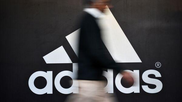 Человек проходит мимо логотипа Adidas в Нью-Дели, Индия