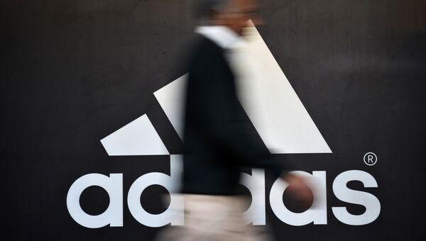 Человек проходит мимо логотипа Adidas. Архивное фото