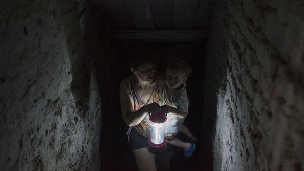 Женщина с ребенком прячется в подвале своего дома в Горловке
