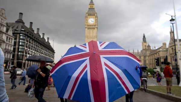 Человек с зонтом с флагом Великобритании у Биг Бена и здания парламента в Лондоне