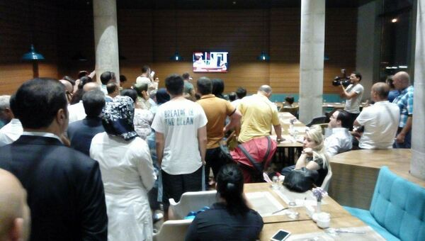Люди смотрят новости в одном из отелей турецкого города Конья. 16 июля 2016