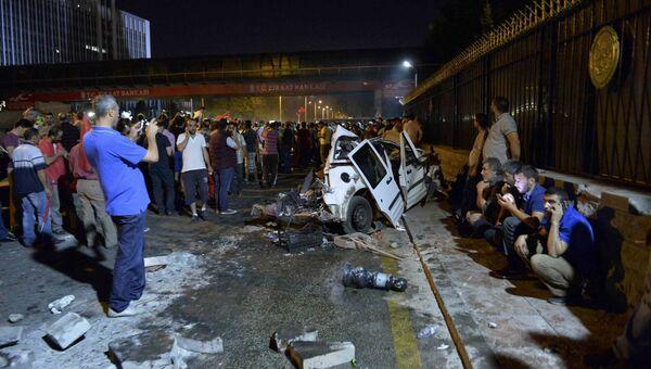Люди у разрушенной полицейской машины в Анкаре. 16 июля 2016