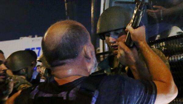 Солдат отдает оружие полицейскому на площади Таксим в Стамбуле. 16 июля 2016