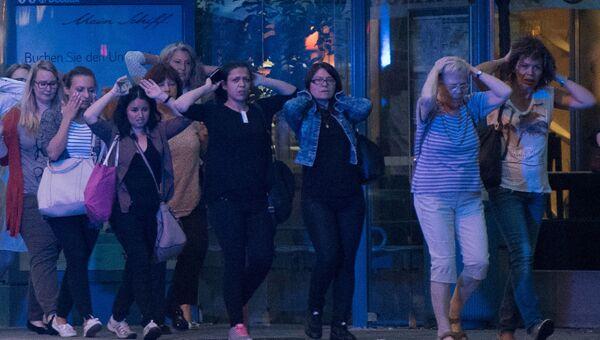 Люди покидают торговый центр в Мюнхене, где неизвестные открыли стрельбу
