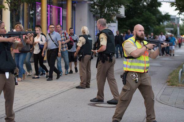 Полиция сопровождает людей, покидающих здание торгового центра, где неизвестные открыли стрельбу