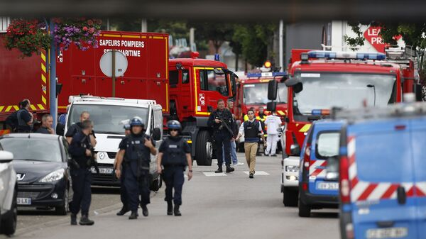 Полицейские и пожарные возле церкви в городке Сент-Этьен-дю-Рувре во Франции, где произошло нападение на священника. 26 июля 2016 года