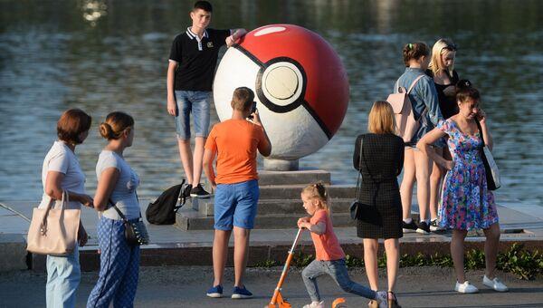 Прохожие рядом с гигантским покеболом из компьютерной игры Pokemon Go от компании Nintendo на набережной городского пруда в Екатеринбуре
