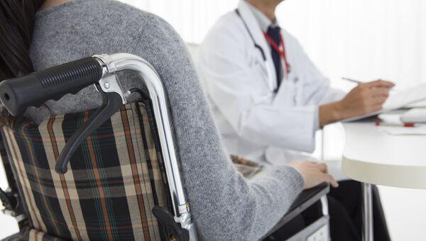 Пациент в коляске на приеме у врача. Архивное фото