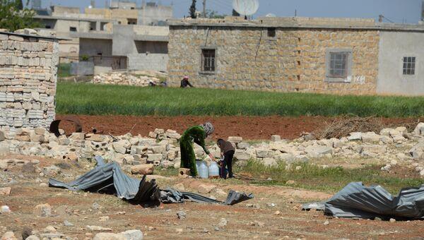 Жители одного из населенных пунктов у дороги из Алеппо в Хомс набирают в емкости воду. Архивное фото