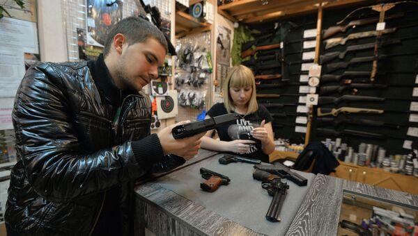 Покупатель рассматривает образцы оружия в оружейном магазине Царская охота в Челябинске