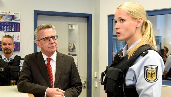 Глава МВД ФРГ Томас де Мезьер разговаривает с сотрудницей полиции Бремена. 10 августа 2016