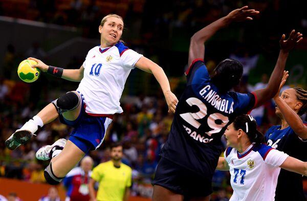 Игроки сборной России и игрок сборной Франции в матче группы В по гандболу между сборными командами на XXXI летних Олимпийских играх
