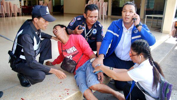 Полицейские с пострадавшим на месте взрыва в Таиланде. 12 августа 2016