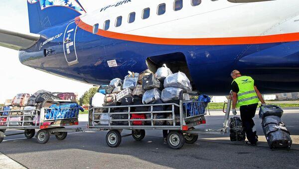 Выгрузка багажа из самолета на взлетно-посадочной полосе аэропорта Храброво в Калининграде
