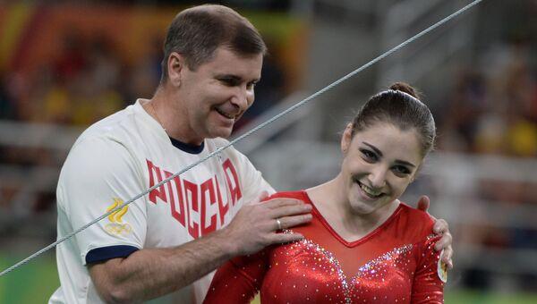 Алия Мустафина с тренером после окончания выполнения упражнений на разновысоких брусьях на XXXI летних Олимпийских играх