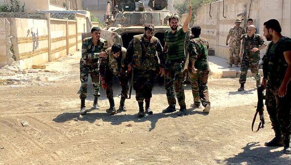 Бойцы сирийской армии выводят раненого при штурме военных училищ на юго-западе Алеппо