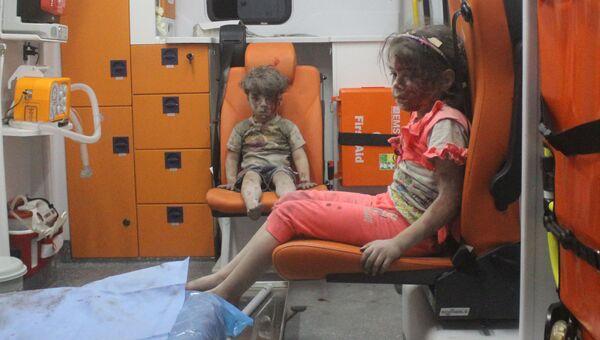Пострадавший при обстреле Алеппо сирийский мальчик Омран и его сестра, 17 августа 2016