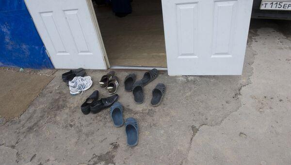 Обувь у двери вагончика где живут иностранные рабочие. Архивное фото