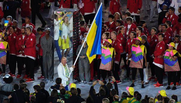 Знаменосец сборной Украины, победитель Олимпийских игр 2000 года в стендовой стрельбе Николай Мильчев во время парада атлетов и членов национальных делегаций на церемонии открытия XXXI летних Олимпийских игр в Рио-де-Жанейро
