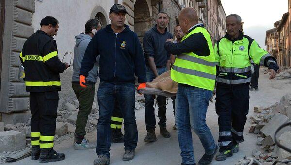 Сотрудники спасательных служб несут на носилках человека, спасенного из-под завалов, в городе Аматриче,