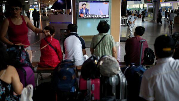 Люди смотрят трансляцию по телевидению Южной Кореи, испытаний баллистической ракеты подводных лодок в КНДР
