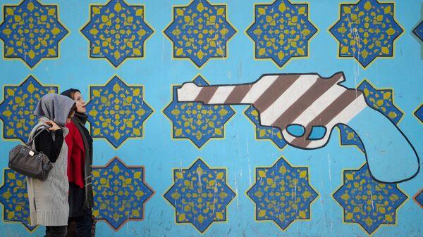 Женщины идут вдоль стены здания бывшего посольства США в Тегеране