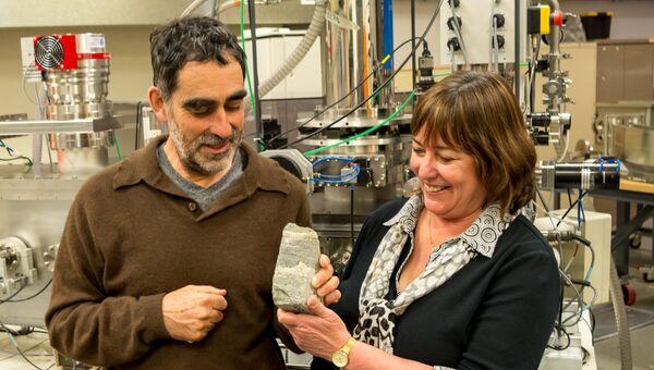 Ученые держат в руках строматолит, чей возраст превышает 3,7 миллиарда лет