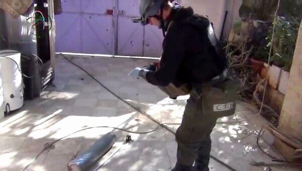 Эксперт из миссии ООН в Сирии обследует гильзу от снаряда в пригороде Дамаска