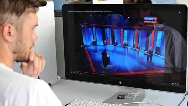 Молодой человек смотрит предвыборные теледебаты с экрана монитора