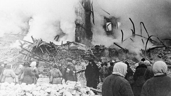 Жители Ленинграда стоят у разрушенного артобстрелом жилого дома в дни блокады