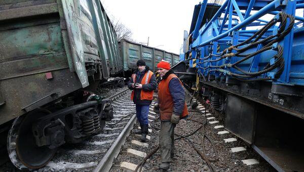 Рабочие осматривают поврежденный товарный вагон в районе станции Ясиноватая в Донецкой области, где в результате подрыва электровоза сошли с рельсов семь вагонов. 17 февраля 2016