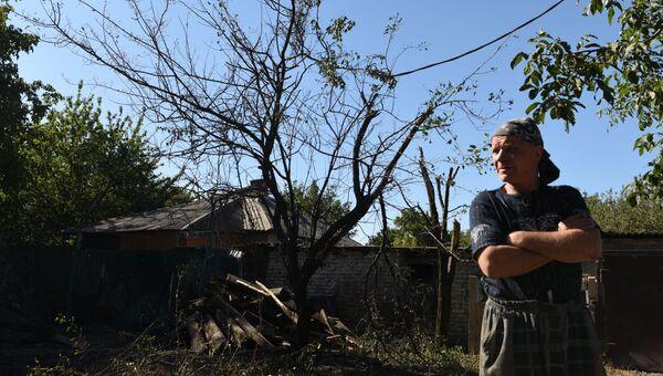 Местный житель осматривает разрушения в результате ночного обстрела. Архивное фото