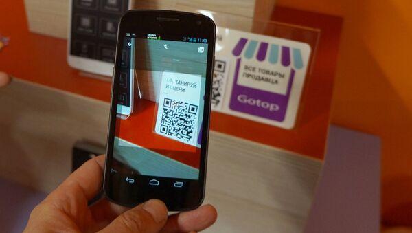 Сканирование QR-кода товара в шоуруме Aliexpress. Архивное фото