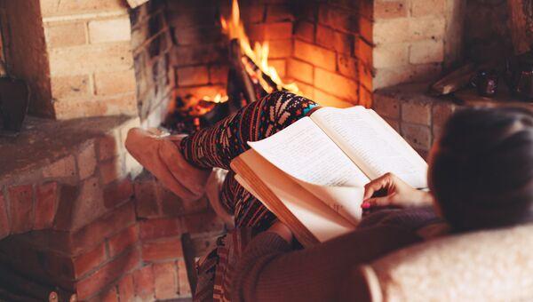 Девушка читает книгу у камина. Архивное фото