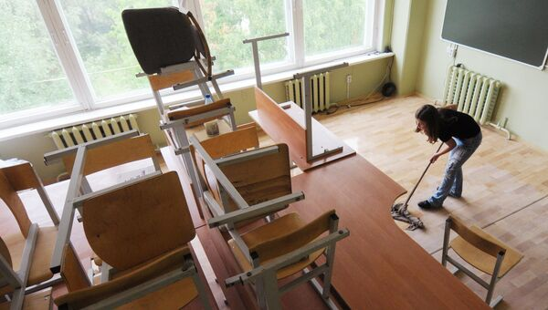 Ученица моет пол в классе. Архивное фото