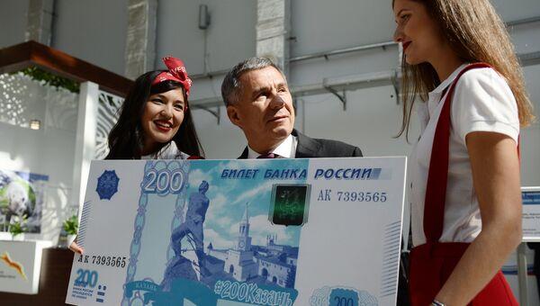 Президент Республики Татарстан Рустам Минниханов фотографируется с образцом банкноты в 200 рублей на международном инвестиционном форуме Сочи 2016. Архивное фото