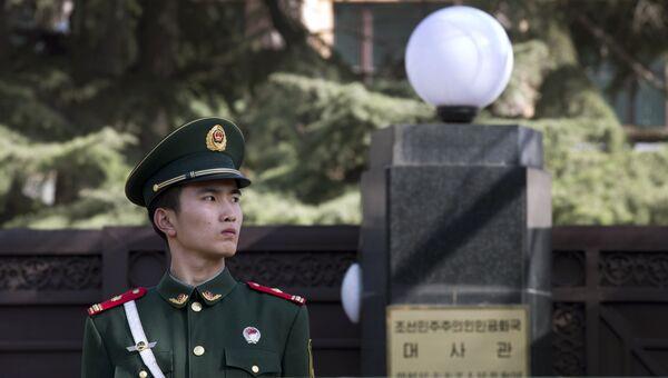 Сотрудник полиции у здания посольства КНДР В Пекине, КНР. Архивное фото