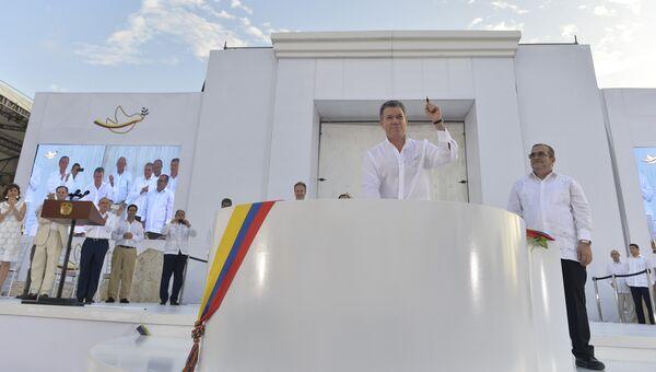 Президент Колумбии Хуан Мануэль Сантос и лидер бывших повстанцев Родриго Лондоньо Эчеверри после подписания соглашения о мире в городе Картахена, Колумбия. 26 сентября 2016. Архивное фото