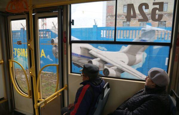 Пассажиры трамвая проезжают мимо граффити, посвященного истории российской авиации