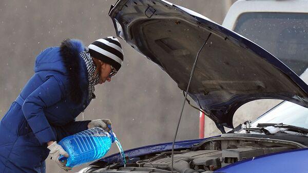 Женщина заливает незамерзающую жидкость для омывания стекол автомобиля