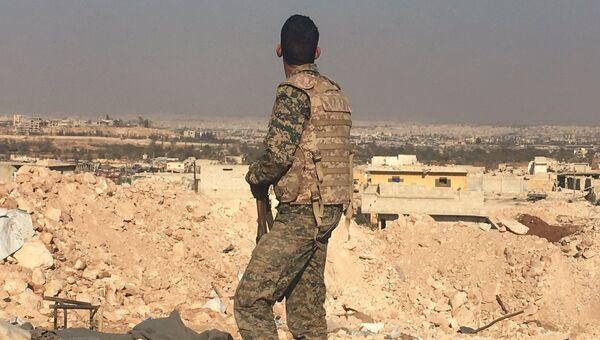 Боец сирийской армии смотрит на город Алеппо с высоты узла мобильной связи к югу от города