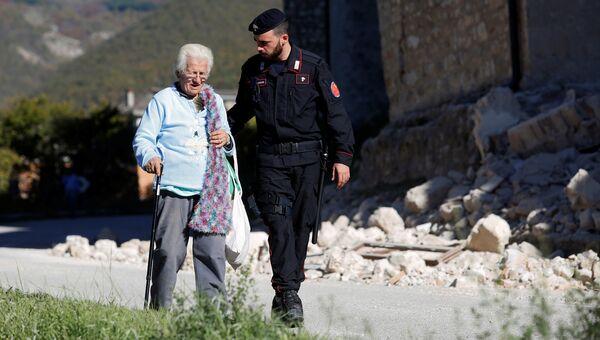 Карабинер c пожилой женщиной в пострадавшей от землетрясения коммуне Норча, Италия